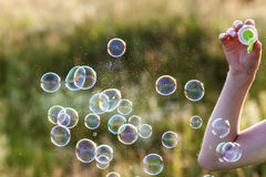 Womans hand with blowing colorful soap bubbles at sunset. Womans hand with blowing colorful soap bubbles at sunset Stock Photo