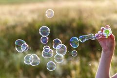 Womans hand with blowing colorful soap bubbles at sunset. Womans hand with blowing colorful soap bubbles at sunset Royalty Free Stock Photography