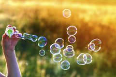 Womans hand with blowing colorful soap bubbles at sunset. Womans hand with blowing colorful soap bubbles at sunset Stock Photography