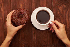 Womans hand with chocolate donut and cup of coffee Royalty Free Stock Images