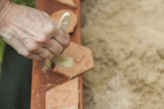 Womans hand cleaning with a brush, three pieces of pottery in a. Sandbox, playing with archaeological remains Royalty Free Stock Photo