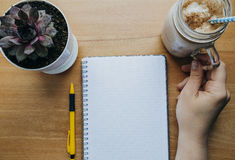 Womans hand with coffee, Notebook, pen, house plant on the table Royalty Free Stock Image