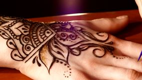 Womans hand decorated with mehendi, on black stock footage