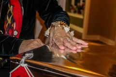 Womans hand with engagement ring opens big gold Christmas present - closeup and selective focus stock images