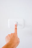 Womans hand with finger on light switch Stock Photo