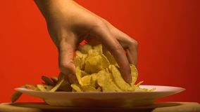 Womans hand grabbing chips from plate, home party with junk food, slow motion