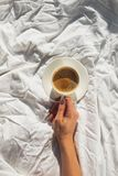 Womans hand holding a cup of coffee on the bed with white linen on the room with natural sunlight. Top view royalty free stock images