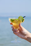 Womans hand holding a glass of cocktail Royalty Free Stock Image