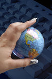 Womans hand holding globe over keyboard Stock Photos