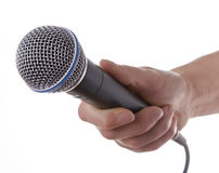 Womans hand holding microphone. Woman presenter holding a microphone in hand royalty free stock photos