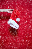 Womans hand holding a Santa Claus hut on red background with sno. W Royalty Free Stock Images