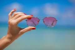 Womans hand holding sunglasses on tropical beach Royalty Free Stock Images