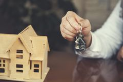 Womans hand key with house model stock photos