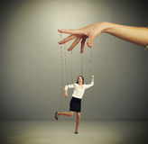 Womans hand manipulating puppet. Over dark background royalty free stock photo