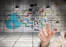 Womans hand pointing against wall background showing global business development Stock Photography