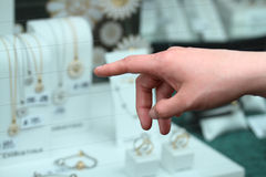 Womans hand pointing at jewellery Stock Images