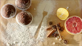 Womans hand putting homemade cakes near condiments. Shot of woman's hand putting cakes near condiments for pastry: lemon, cinnamon sticks and grape-fruit on the stock video footage