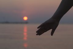 Womans hand silhouetted against a sunset Stock Photo