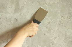 Womans hand with a spatula plasters wall Stock Photography