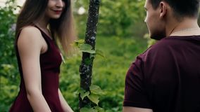 Womans hand touches leaves. Beautiful young woman walks in front of her man, turns head Backview slow mo, steadicam shot stock video
