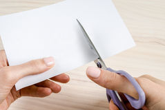 Female hands cutting paper with scissors Royalty Free Stock Photos
