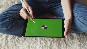 Womans hands draw with stylus on chromakey screen of graphic tablet, top view, closeup. Illustrator draws on digital