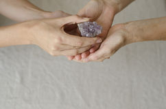 Womans hands giving an amethyst crystal one to another Stock Images