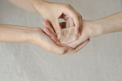 Womans hands giving a quartz crystal one to another Royalty Free Stock Photos
