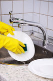 Womans hands in the gloves wash plate vertical 0908 Royalty Free Stock Images