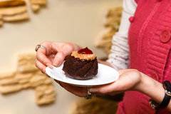 Womans hands hold a cake on a plate Royalty Free Stock Image
