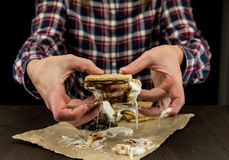 Womans Hands Hold a Gooey Marshmallow Smore. With dripping melted marshmallow Royalty Free Stock Image