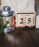 Womans hands hold wooden calendar with 25 december date on the dark wooden background. New year and Christmas concept, stock image