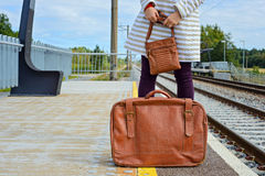 Womans hands holding bag and suitcase at station Stock Photo