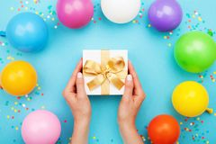Womans hands holding gift or present box on blue table decorated colorful balloons and confetti. Flat lay style. royalty free stock photos