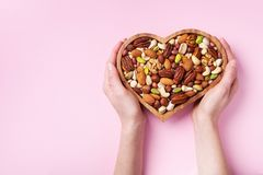 Womans hands holding heart shaped bowl with mixed nuts on pink table top view. Healthy food and snack. Flat lay royalty free stock photography