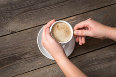 Womans hands holding hot cup of coffee. View from top on a warm coffee cup. Stock Images