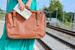 Womans hands holding a map and suitcase at station Royalty Free Stock Photo