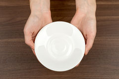 Womans hands holding saucer Royalty Free Stock Photography