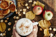 Womans hands with Hot cocoa  with popcorn, apple, cakes, leaves. Womans hands with Hot cocoa coffee with popcorn, apple, cakes, leaves on the old wooden boards Royalty Free Stock Image