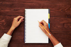 Womans hands with notebook on table Royalty Free Stock Photos