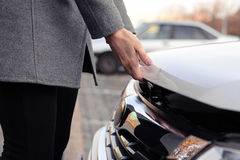 Womans hands open the bonnet at outdoor Stock Photo