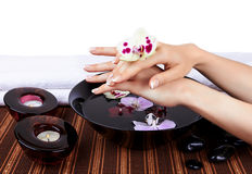 Womans hands with orchids and bowl of water Stock Photo