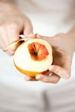 Woman's hands pare red apple Stock Photo
