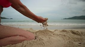 Womans hands playing with sand at exotic beach and blurred ocean backdrop. summer vacation concept.  stock video footage