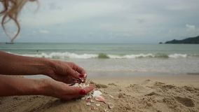Womans hands playing with sand at exotic beach and blurred ocean backdrop. summer vacation concept.  stock footage