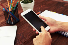 Womans hands with smartphone over table Royalty Free Stock Photos