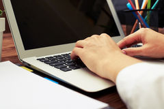 Womans hands typing on keyboard on workspace Stock Photography