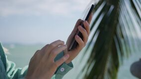 Womans hands using smartphone over background sea and palm trees. Girl touching screen. Closeup womans hand using smartphone over background sea and palm trees stock video