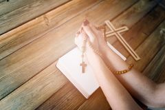 Womans hands with wooden rosary and Holy Bible Royalty Free Stock Photos