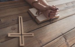 Womans hands with wooden rosary and Holy Bible Stock Photos